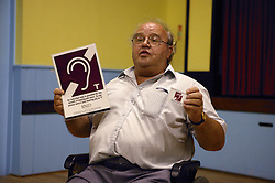 Disabled man speaker at Disability Awareness Forum; showing induction loop sign,