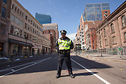 A Boston police officer stands guard on Boylston street, near the finish line of the Boston Marathon and the site of deadly twin bombings a day earlier, in Boston, Massachusetts, USA on 16 April 2013. At least three people died and more than a hundred were injured in an apparent terrorist attack in the northeastern US city.
