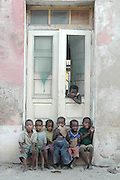 Children sit in the door way of a crumbling portuguese building..Ilha De Mocambique (Mozambique Island), Northern Mozambique, Africa.© Demelza Cloke