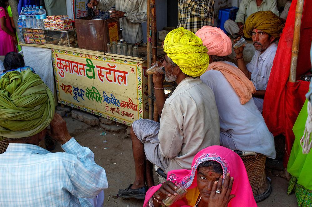 Some rajasthani people having tea in a busy Pushkar market during Pushkar Camel Fair, Rajasthan.