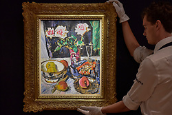 "© Licensed to London News Pictures. 17/11/2017. London, UK.  London, UK.  17 November 2017.  A staff member views ""Still Life of Pink Roses with Fruit and a Glass"", by George Leslie Hunter (Est. GBP 200-300k).   Preview upcoming auctions of Modern & Post War British Art and Scottish Art taking place at Sotheby's, New Bond Street, on 21 and 22 November. Photo credit: Stephen Chung/LNP"