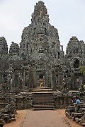 Bayon Temple which stands in the centre of the walled temple complex of Angkor Thom, Siem Reap Province, Cambodia, South East Asia.  The temple was built around 1190 AD by King Jayavarman VII as a Buddhist temple, but it incorporates elements of Hindu cosmology.  In the centre is a statue of Buddha with a yellow tunic.  (photo by Andrew Aitchison / In pictures via Getty Images)