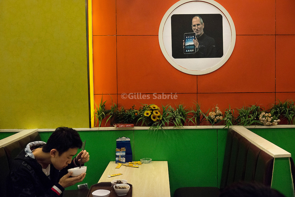 For a story by Keith Bradsher: final chapter of I-Economy.Chengdu November29 2012.A Foxconn worker having his dinner under a picture of Steve Jobs handling an Ipad, in a popular fast food restaurant..Gilles Sabrie for the New York Times.Slug: I-Economy