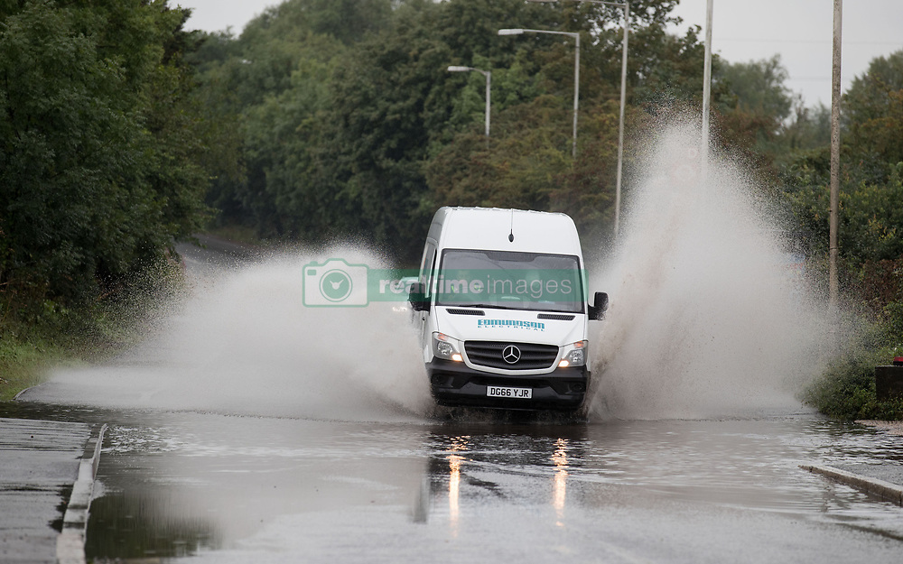 A van goes through a large puddle near Colnbrook, Berkshire as a yellow weather warning for rain has been issued for parts of the UK.