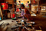 Kachin refugee housewives ai Je Yang Hka near China Myanmar boarder Lai Za. A refugee granny cooking dinner for her family.