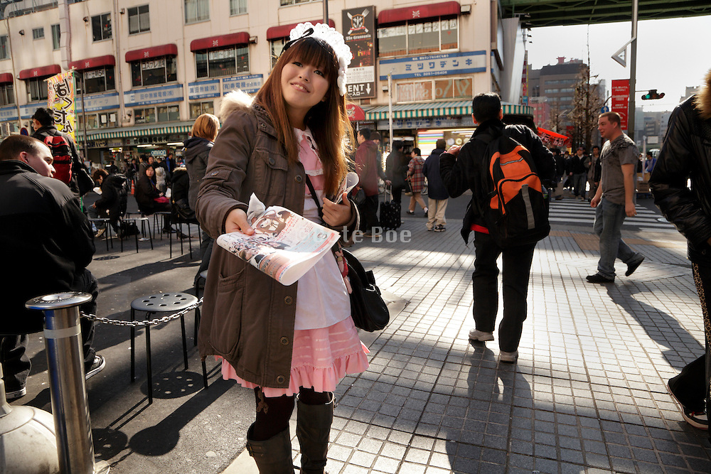 anime dressed up girl in Akihabara district in Tokyo handing out flyers for maid cafe