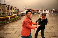 A young couple hold hands in front of the Jokhang Temple in Lhasa, the capital of Tibet in western China. (Photo/Scott Dalton)
