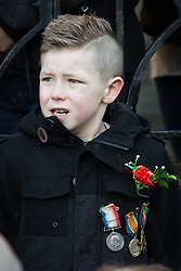 © Licensed to London News Pictures . 10/11/2013 . Bury , UK . A boy in the crowd wearing medals . Remembrance Sunday service at Bury Parish Church , Greater Manchester today (Sunday 10th November 2013) . Photo credit : Joel Goodman/LNP