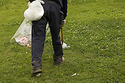 Israel, Tel Aviv, park employee collecting litter with the aid of a pointed stick