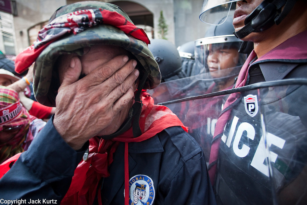 Apr. 12, 2010 - BANGKOK, THAILAND: A Red Shirt security guard wipes his face while he protects Thai police and tries to hold back the crowd in front of the Prime Minister's house on Soi 31 off of Sukhumvit Rd in Bangkok Monday. The funeral cortege for the Red Shirts killed in the violent crackdown Saturday wound through Bangkok and parts of the procession passed by the Prime Minister's home. Thousands of mourners came out to pay respects for dead Red Shirts. 21 people, including 16 Thai civilians were killed when soldiers tried to clear the Red Shirts' encampment in Bangkok. Thousands more came out to call for the government of Thai Prime Minister Abhisit Vejjajiva to step down. Today Gen. Anupong Paojinda, the Chief of Staff of the Thai Army, reiterated that the Army would not use violence to break up the protests and joined the call for the Prime Minister to call new elections. This is the beginning of Songkran, Thai New Year's week, and the government has cancelled the official festivities fearing more violence. It was during last year's Songkan festivities that the Thai Army and police used force to break up the Red Shirt protests. That protest is now called the Songkran Riots.         Photo By Jack Kurtz