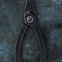 Vintage small pliers lying closed on tarnished metal sheet