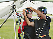 Hang glider pilot Thomas Atkins, right, checks Emmanuelle Dimarsky's helmet before they were towed into the sky by an ultralight aircraft at Randall Airport in Middletown on Friday, Aug. 23, 2013. The hang glider rides are run by Hangar 3.