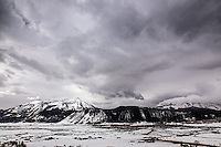 A weather system rolls into Crested Butte, Colorado in late winter while snow still covers the valley below Whetstone Mountain.