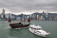 Ancient Chinese junk passing a modern yacht in Victoria harbour, Hong Kong.