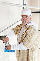 Portrait of a cheerful mature man holding construction equipment