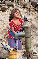 Young Nepali girl pumping water, Bardiya, Nepal