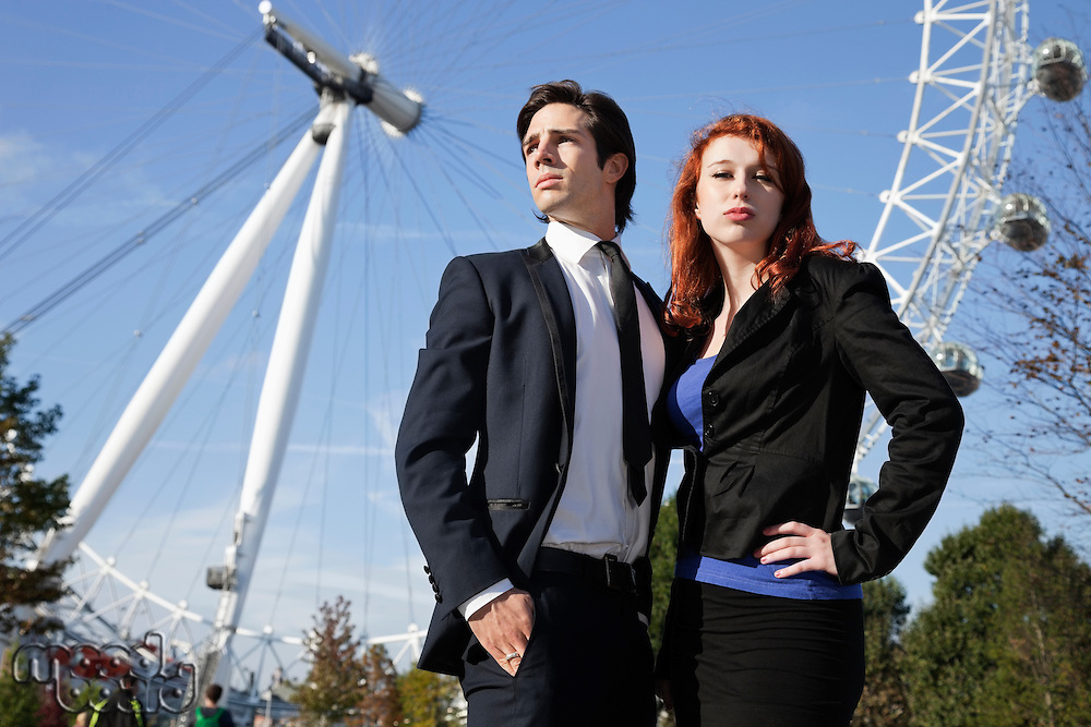Portrait of confident young businesswoman standing against London Eye with colleague, London, UK