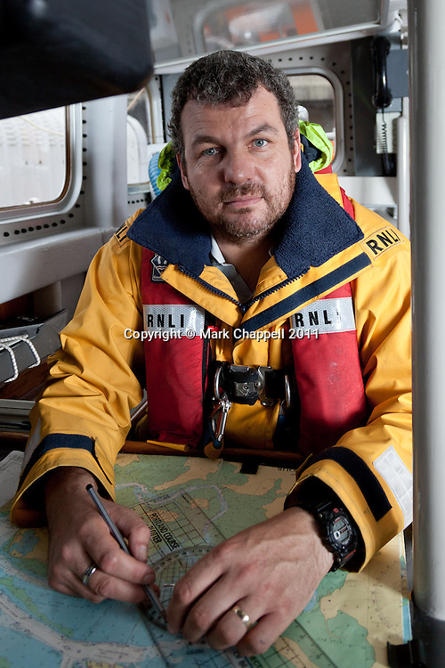 POOLE, UNITED KINGDOM. October 5 2011. Richard Skerman sits for a portrait at the chart table of RNLI City of Sheffield, the Tyne Class All Weather Lifeboat (ALB) based at Poole RNLI Station. Mr Skerman is the helm of Sergeant Bob Martin, the Poole based Atlantic 85 Class Inshore Lifeboat (ILB), assistant mechanic on the ALB and works for internationally renowned boat builders, Sunseaker. Since January 1 2011 RNLI Poole has launched their ILB 88 times, the ALB 27 times and Richard himself has taken part in 63 of those launches. According to him these figures are lower than he would normally expect given the figures for previous years. © Mark Chappell 2011.