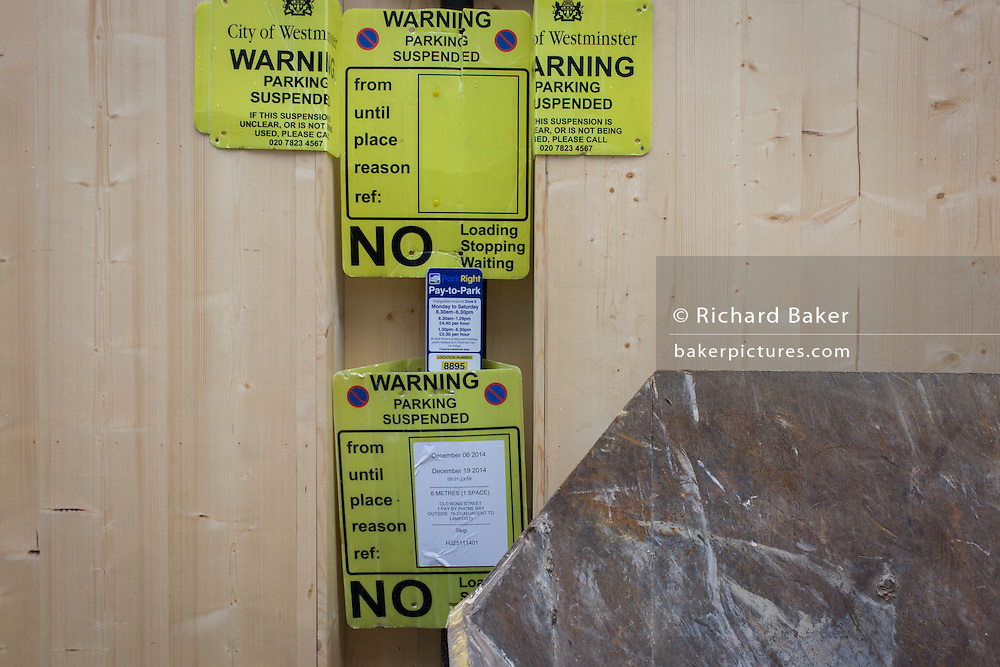 Parking suspension signs attached to construction hoardings in London's New Bond Street.