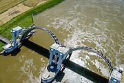 Nederland, Gelderland, Gemeente Overbetuwe, 09-06-2016; stuw bij Driel in de Neder-rijn. In verband met het hoge water ten gevolge van overvloedige regenval in Duitsland is de stuw is geopend, een uitzonderlijke situatie in deze periode van het jaar. De stuw bij Driel, de Kraan van Nederland, zorgt voor afvoer van het water van de Rijn via Nederrijn en Lek. Het stuwensemble wordt gerenoveerd en gemoderniseerd.<br /> Due to the hight water levels as a result of heavy rainfall in Germany, the weir has been opened, an exceptional situation in this time of the year.<br /> The weir at Driel, nicknamed 'main valve of the Netherlands', provides drainage of water from the Rhine via the Lower Rhine and Lek to the sea. The ensemble of locks and weir will be renovated and modernized.<br /> <br /> luchtfoto (toeslag op standard tarieven);<br /> aerial photo (additional fee required);<br /> copyright foto/photo Siebe Swart