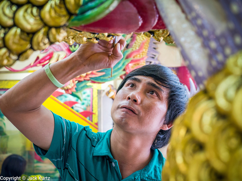"24 FEBRUARY 2013 - BANGKOK, THAILAND: An attendant paints the dragons the guard the entrance to the ""coffin temple"" of the Ruamkatanyu Foundation next to Wat Hua Lamphong. The Ruamkatanyu Foundation provides coffins for Bangkok's indigent and emergency medical services for accident victims in Bangkok. Wat Hua Lamphong is a Royal Buddhist temple, third class, in the Bang Rak District of Bangkok, Thailand. It is located on Rama IV Road, approximately 1 km from the city's main Hua Lamphong railway station. An entrance to Sam Yan Station on the Bangkok metro (subway) is located outside the main entrance to the temple compound on Rama IV. Wat Hua Lamphong was renovated in 1996 to mark the 50th anniversary of the ascension to the throne of King Bhumibol Adulyadej (Rama IX) in 1996. The royal seal of what became known as the Kanchanapisek, or Golden Jubilee, year, showing two elephants flanking a multi-tiered umbrella, are featured in the temple's remodeling.     PHOTO BY JACK KURTZ"