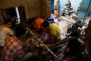 A family home in the slum surrounding Firozabad, renowned as the 'glass city', in  Uttar Pradesh, northern India, has been transformed into a small-scale workshop where young boys and girls are aligning the ends of bracelets produced in coils by factories nearby. Due to extreme poverty, over 20.000 young children are employed to complete the bracelets produced in the industrial units. This area is considered to be one of the highest concentrations of child labour on the planet. Forced to work to support their disadvantaged families, children as young as five are paid between 30-40 Indian Rupees (approx. 0.50 EUR) for eight or more hours of work daily. Most of these children are not able to receive an education and are easily prey of the labour-poverty cycle which has already enslaved their families to a life of exploitation. Children have to sit in crouched positions, use solvents, glues, kerosene and various other dangerous materials while breathing toxic fumes and spending most time of the day in dark, harmful environments. As for India's Child Labour Act of 1986, children under 14 are banned from working in industries deemed 'hazardous' but the rules are widely flouted, and prosecutions, when they happen at all, get bogged down in courts for lengthy periods. A ban on child labour without creating alternative opportunities for the local population is the central problem to the Indian Government's approach to the social issue affecting over 50 million children nationwide.
