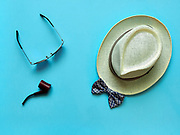 Pipe and glasses lying near straw hat and bow tie on blue background