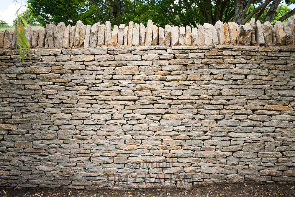 Newly built dry stone wall - drystone - constructed of new Cotswolds stone using traditional old methods, UK