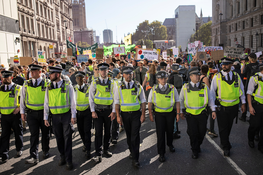 © Licensed to London News Pictures. 20/09/2019. London, UK. Police escort thousands of protesters as they march along Whitehall as part of the Global Climate Strike in London. Protests about the climate crisis are being led by young people in cities around the world, with millions expected to attend. Photo credit: Rob Pinney/LNP