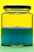 closed glass jar containing a blue liquid object on yellow green background
