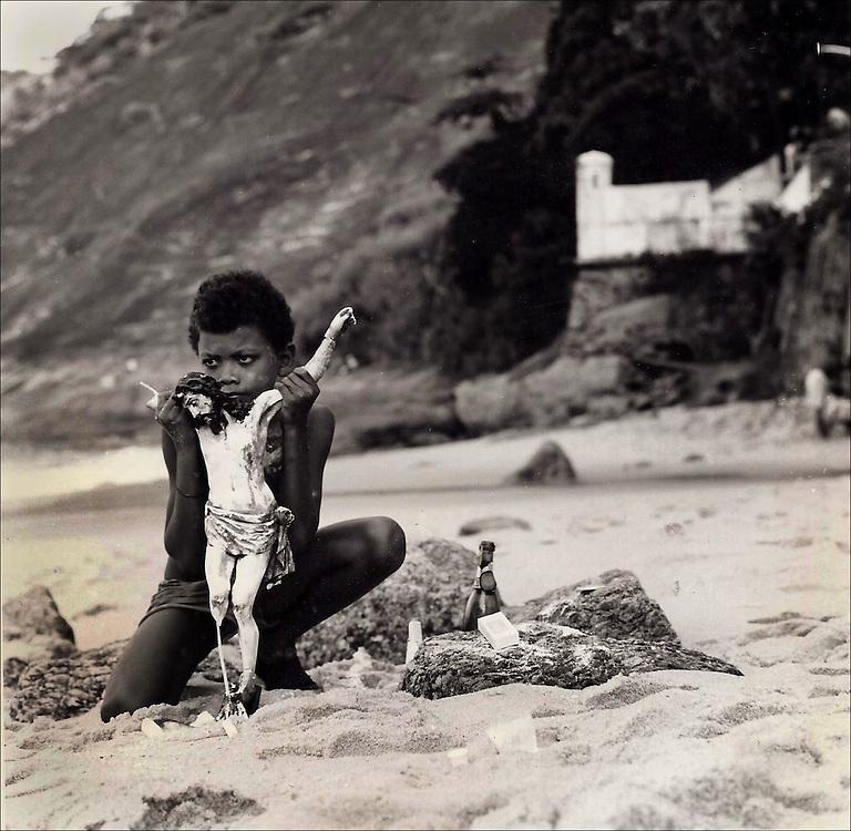 Young boy performs religious ritual on beach in Rio de Jinero.  1988