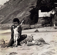 Young boy performs religious ritual on beach in Rio de Jinero.  1988