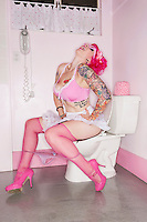Pink haired woman sitting on toilet seat
