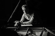 Black and white portrait of Jazz artist David Goldblatt at the piano with dramatic lighting.