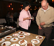 Lynn Domescik gets a slice of cake from Karl Dean as Riverside Area Chamber of Commerce hosts an International Night featuring Indian and American food at the Filling Station Sports Bar & Grill in Riverside, Monday, March 26, 2012.  Owner Doctor Suresh Gupta prepared Indian cuisine including Bean Sprout Cucumber Salad, Butter Chicken, Samosas, Rice/Naan Bread and Veggie Khorma.