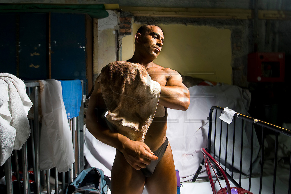 For two years in a row, in a rundown theater in Porto, the Portuguese National Championship of Bodybuilding WABBA happened. Several athletes, from allover the country came to this one day competition. <br /> These are photos from the backstage, where the athletes exercise and get body paint for the stage presentation. The muscles and the gold and brown colors get ready in the confusion of tubes, abandoned wood from different theater plays, photos from the past and dressing rooms with 100 years old. <br /> Mario after the competition, cleaning the paint.