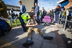 © Licensed to London News Pictures. 10/10/2019. London, UK. Police arrest an Extinction Rebellion protester at London City Airport as passengers with suitcases walk. past. Protesters planned to occupy the terminal building in a 'Hong Kong-style' shutdown as part of ongoing protests calling on government departments to tackle the Climate Emergency. Photo credit: Rob Pinney/LNP