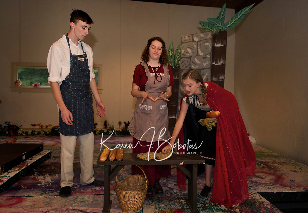 """Little Red (Kathryn Osburn) helps herself to the Baker and his wife's (Chris Renaud and Chelsea Sasserson) breads during dressing rehearsal for SKYT's musical """"Into The Woods"""" at the Gilford Methodist Church.  (Karen Bobotas/for the Laconia Daily Sun)(Karen Bobotas/for the Laconia Daily Sun)"""