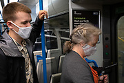Rail passengers on a train service through south London wear facial coverings during the Coronavirus pandemic, on 24th August 2020, in London, England.