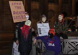 "London, December 23rd 2014. Online activism group Anonymous march through London from the City to the BBC's HQ on Great Portland Street in protest against alleged biases and coverups of a ""paedophile ring"". PICTURED: A protester's banner demands that the ""Death Eaters"" be stopped."