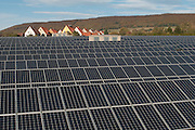 Freiflächen-Photovoltaik-Anlage  mit Sicht auf Dächer von Einfamilienhäusern in einem Dorf im Weserbergland. | Big photovoltaic power plant in the Weser Hills, roofs of family houses.