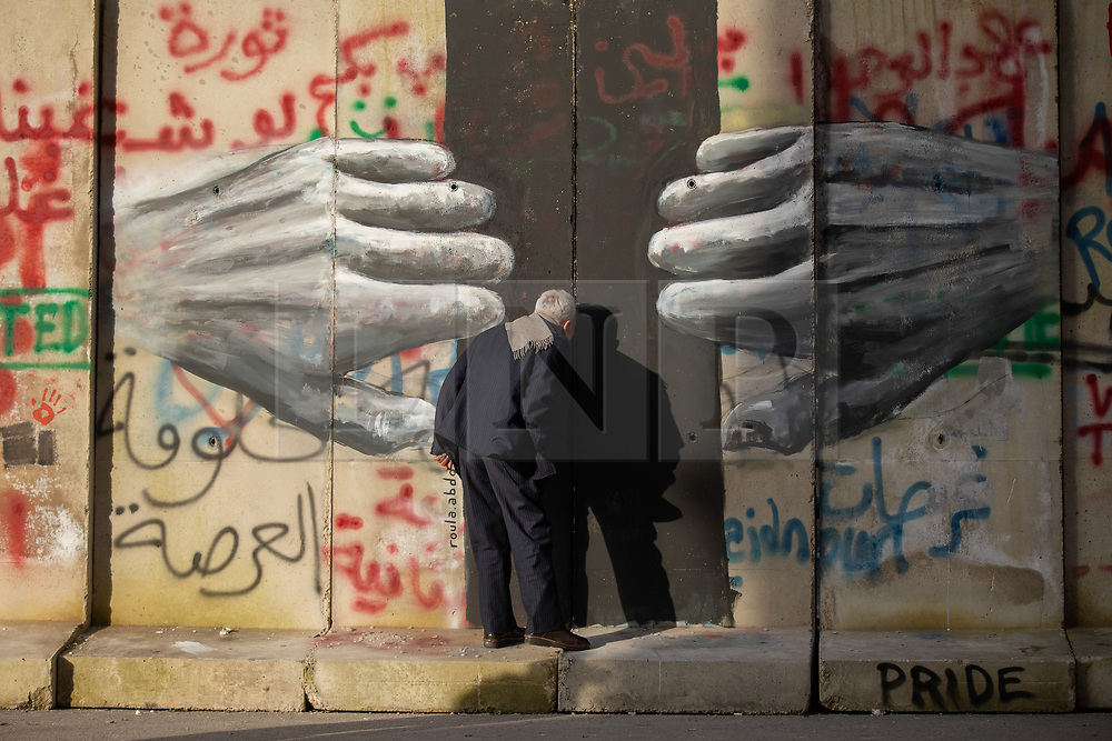 © Licensed to London News Pictures. 27/01/2020. Beirut, Lebanon. A man peers through a gap in a graffitied security wall around the government buildings in Downtown Beirut, as the government votes on the 2020 budget. Anti government demonstrators have been campaigning against government corruption and economic crisis for 103 days in Lebanon. Photo credit : Tom Nicholson/LNP