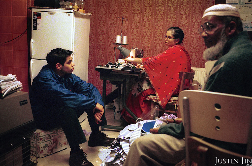A Bengladeshi boy talks with his family in Oldham, a poor mill town in northern England where Muslims and Christians live in virtual apartheid...Oldham is scene of heavy rioting by Asians in the summer of 2001...Many say they do not feel part of the British community, and the war in Afghanistan only confirmed the West's animosity. In this highly segregated pocket of Islam, the old and young, good and bad are pushed to the same fold by a shared sense of alienation in a Western society that they feel is oppressive - both locally and around the world. ..Photo by Justin Jin, Northern England, November 2001.