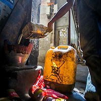 Jan 3, 2013 - A repair shop employee tries to recover every drop of fresh motor oil from the used cans in the Cambodian capital city of Phnom Penh.<br /> <br /> Story Summary: Amidst the feverish pace of Phnom Penh&rsquo; city streets, a workhorse of transportation for people and goods emerges: Bicycles, motorcycles, scooters, Mopeds, motodups and Tuk Tuks roam in place of cars and trucks. Almost 90 percent of the vehicles roaming the Cambodian capital of almost 2.3 million people choose these for getting about. Congestion and environment both benefit from the small size and small engines. Business is booming in the movement of goods and and another one million annual tourists in Cambodia&rsquo;s moto culture.