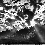 The sun breaks through an opening in late afternoon light over the Teton Range in Grand Teton National Park Wyoming.