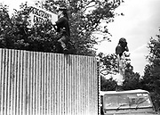 Danny and Stewart climbing a fence and placing an entrance banner at Glastonbury, 1989.