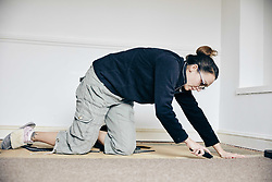 February 14, 2018 - Woman using knife to cut away carpet on floor (Credit Image: © Mint Images via ZUMA Wire)