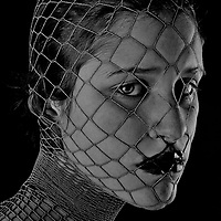 Close up of female teenagers face with netting looking at camera