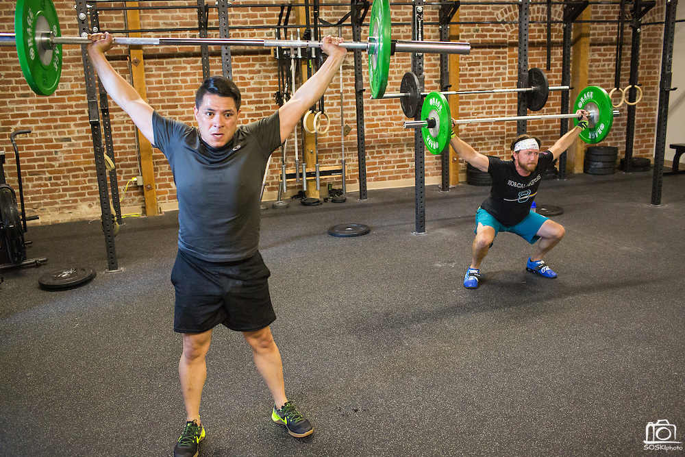 Juan Carlos Miranda, foreground, and Cody Fowler perform a squat clean and press during a CrossFit program at ThirdSpace Fitness in San Jose, California, on July 6, 2015. (Stan Olszewski/SOSKIphoto for Content Magazine)