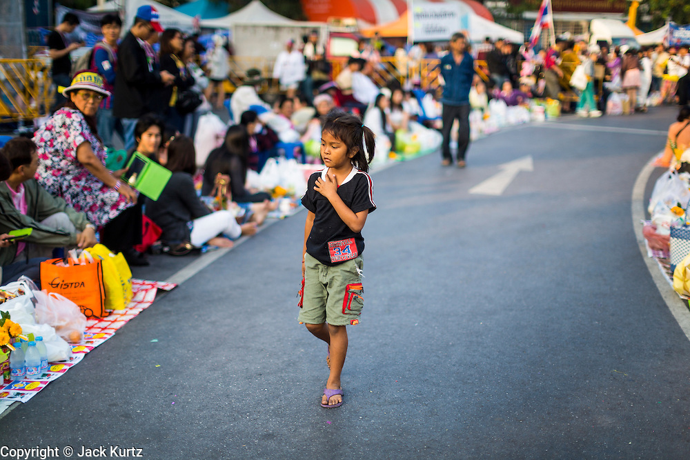 01 JANUARY 2014 - BANGKOK, THAILAND:  A child walks between rows of merit makers before a merit making ceremony. Thousands of anti-government protestors are camped out at Democracy Monument in central Bangkok protesting against the government of Yingluck Shinawatra. The protest leader, Suthep Thaugsuban, has called for residents of the Thai capital to rise up against Yingluck. He has promised to shut the city of 12 million down in his final push to overthrow the government. About 100 members of the Thailand's Buddhist clergy visited the protest site Wednesday morning for a special merit making ceremony for the protestors.    PHOTO BY JACK KURTZ